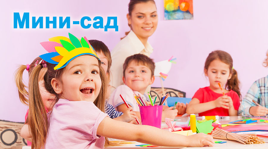Portrait of happy little girl in early developing class in kindergarten with teacher and other children on background